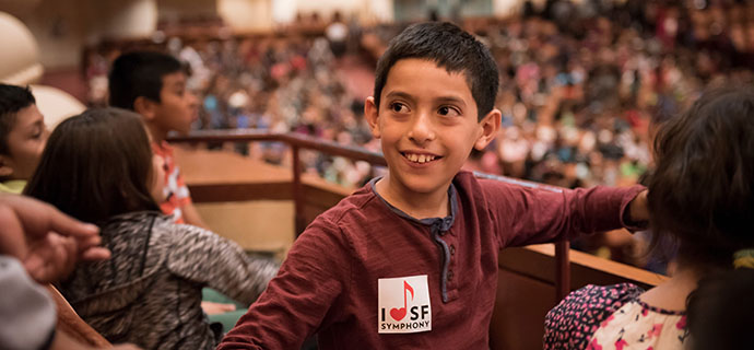 A student wearing an SF Symphony sticker sits in Davies Symphony Hall
