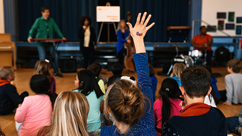 A girl raising her hand during an AIM program