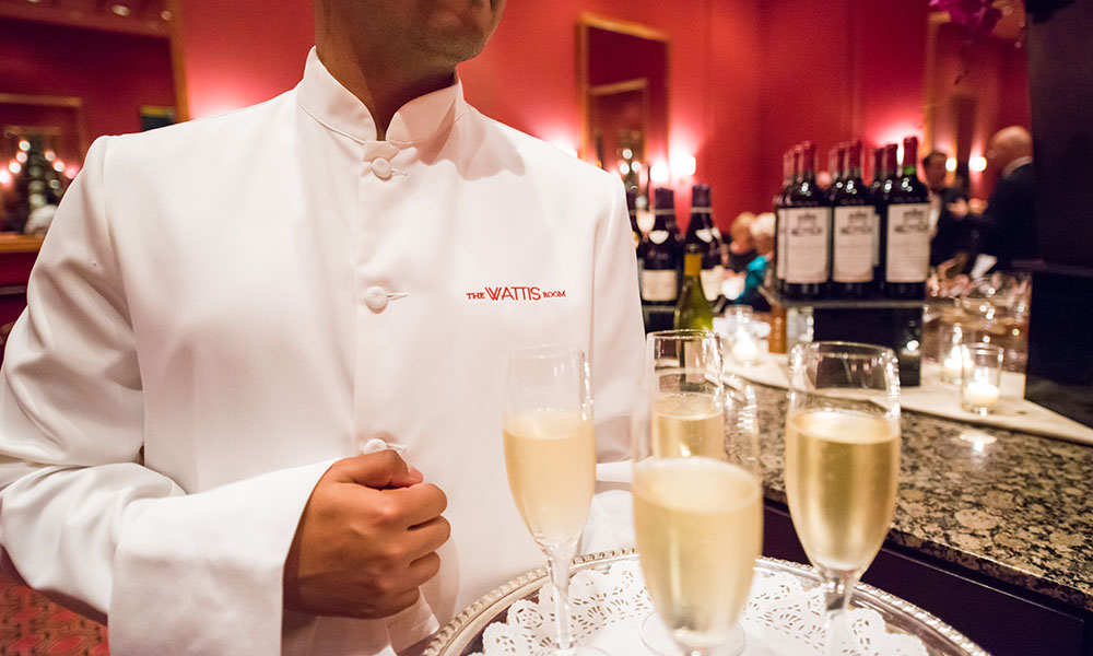 A Wattis Room waiter carries champagne