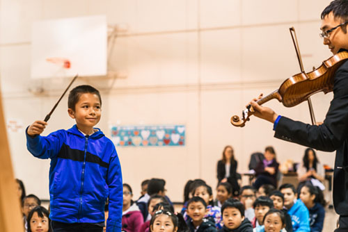 A child conducts a violinist during an AIM concert
