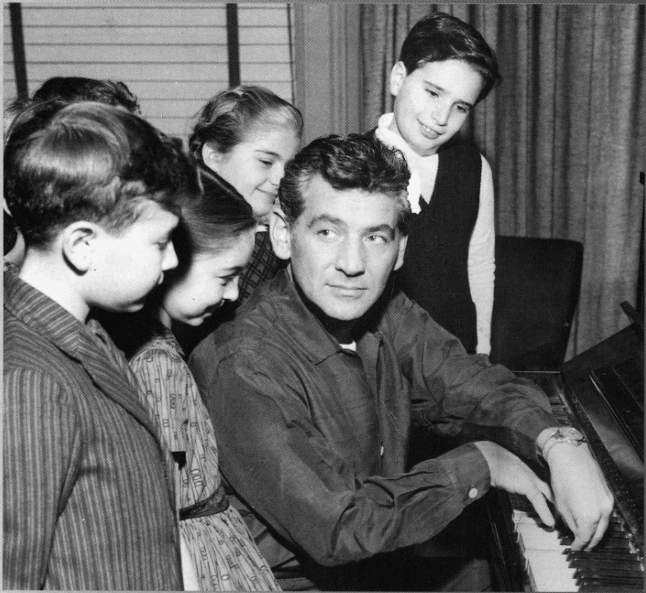Leonard Bernstein at a piano with a crowd of children