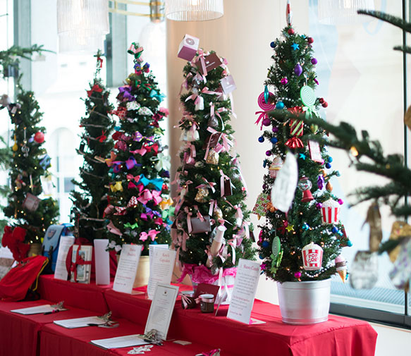 Mini-Trees for auction, decorated with colored ornaments.